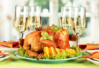banquet table with roast chicken and glasses of wine.