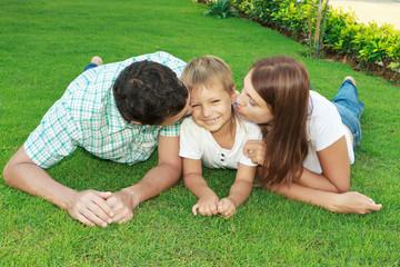 Родители целуют сына лежа на траве