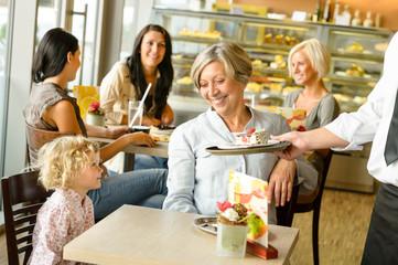 Grandmother and grandchild waiting cake order cafe