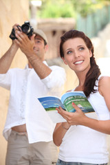 Tourists with camera and travel guide