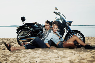 Fototapete - Boyfriend and girlfriend rider sitting on sand beach by bike