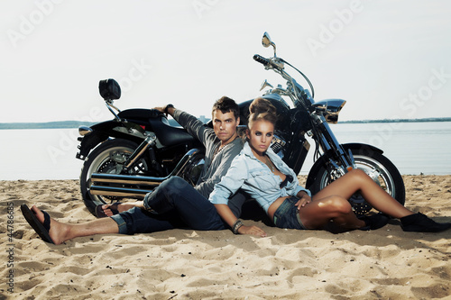 Fototapete Boyfriend and girlfriend rider sitting on sand beach by bike