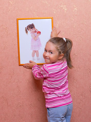 Smiling girl hanging up a self portrait