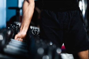 Hand of a man choosing a dumbbell out of set of black dumbbells