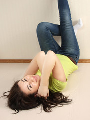 A woman lying on the floor with legs up, indoors