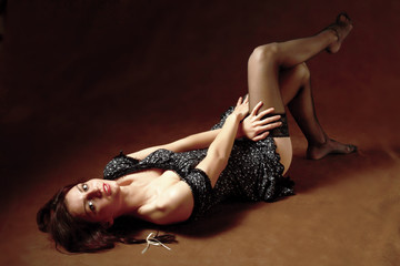 A girl lying on the floor, isolated on black background