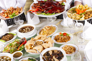 mixed Chinese food with chef holding some dishes