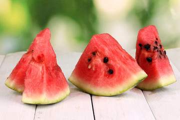 Sweet watermelon slices on wooden table on natural background