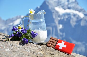 Wall Mural - Swiss chocolate and jug of milk against Alps. Switzerland