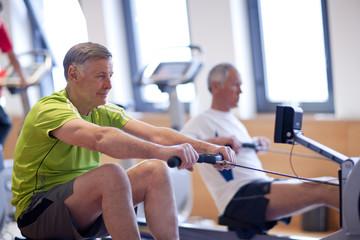 Senior men exercising on rowing machines in gym