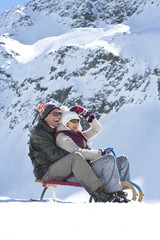 Smiling senior couple sledding on snowy mountain