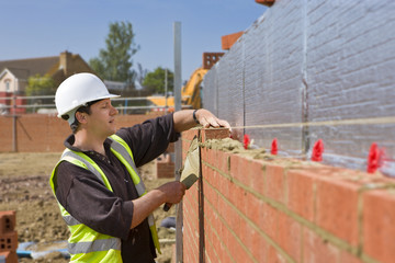 Bricklayer laying brick wall