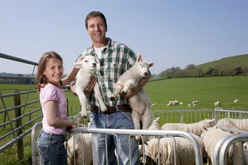 Portrait of shepherd and daughter with sheep in pasture