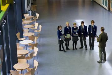 Teacher and students in school uniforms standing in school corridor