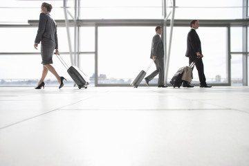 Business people pulling suitcases in airport