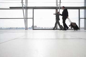 Businessmen pulling suitcases in airport