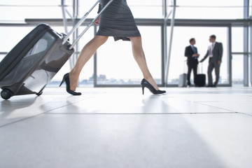 Businesswoman pulling suitcase in airport