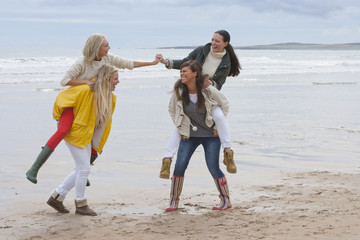 Smiling young women in piggyback battle on beach
