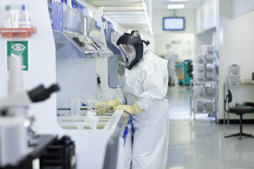 Scientist in clean suit working in silicon wafer manufacturing laboratory