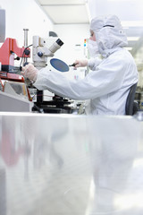 Scientist at microscope in clean suit examining silicon wafer in clean room laboratory