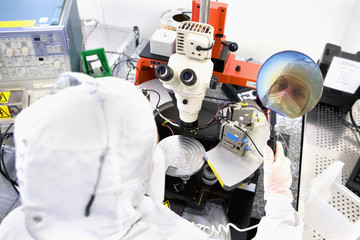 Reflection of scientist in silicon wafer next to microscope in clean room laboratory