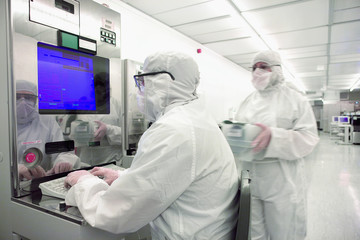 Scientist in clean suit working at computer in silicon wafer manufacturing clean room