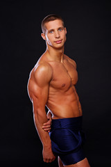An athlete is posing in a studio