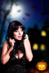 attraktive schwarzhaarige Frau vor Halloween Hintergrund