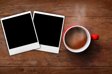 Red cup coffee with frame picture on wood background