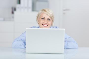 lächelnde frau im büro mit ihrem laptop