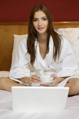Portrait of beautiful woman with cup on bed