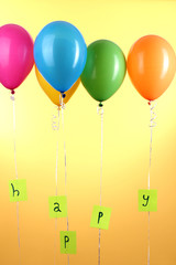 Colorful balloons keeps word happy on yellow background