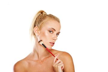 Beautiful woman with cosmetics brush