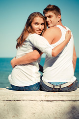 Happy young couple sitting by blue sea over blue sky background