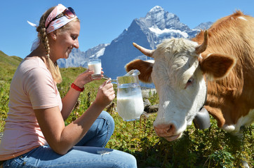 Wall Mural - Girl with a jug of milk and a cow. Switzerland