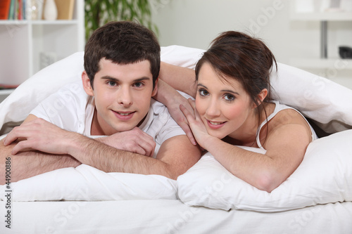 young couple laying in bed together stock photo and royalty free images on pic. Black Bedroom Furniture Sets. Home Design Ideas