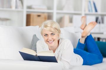 entspannte frau liest ein buch auf dem sofa