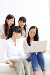 ノートパソコンを見る女の子四人