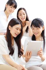 タブレットPCを見る女の子四人