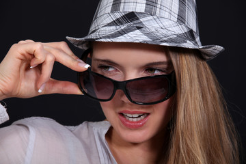 Woman with glasses taking off her hat