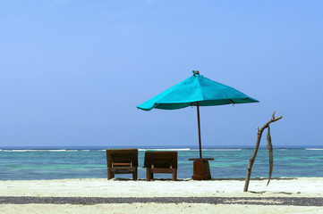Tropical beach with deck chairs and parasol
