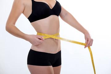 Woman in underwear measuring her waist