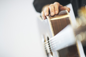 Bright side view of an acoustic western guitar with player