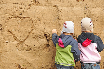 two children draw on the sand wall