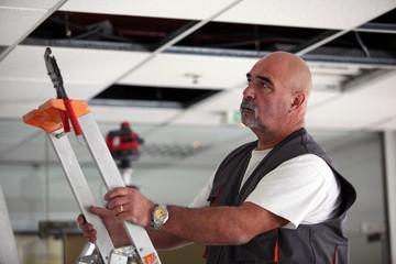 Obraz Man moving a ladder - fototapety do salonu