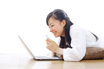クレジットカードでオンラインショッピングをする女の子