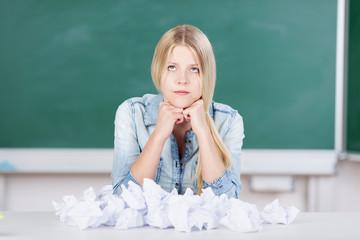 schülerin sitzt vor zerknülltem papier
