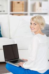 lächelnde frau sitzt mit laptop im wohnzimmer