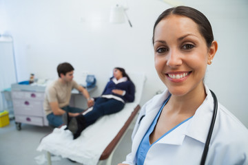 Doctor smiling in hospital room with patient