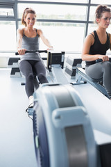 Two people training on row machines